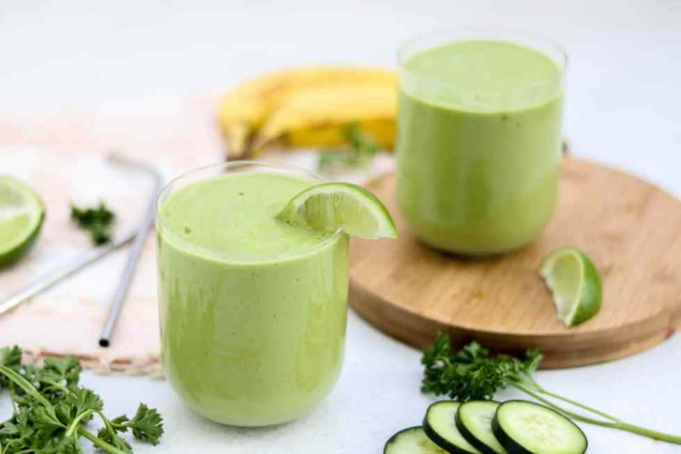 Green smoothie with a lime wedge in a small glass cup for gut healing.