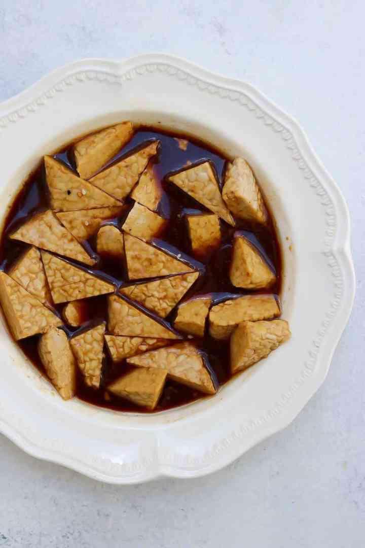 Vegan tempeh recipe marinating in sesame sauce in a white bowl.