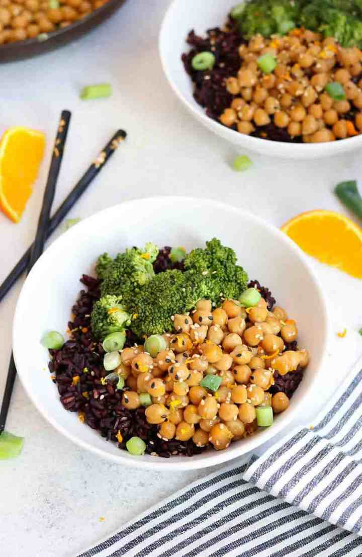 Two bowls with black rice, orange chickpeas, and steamed broccoli with a blue stripped napkin.