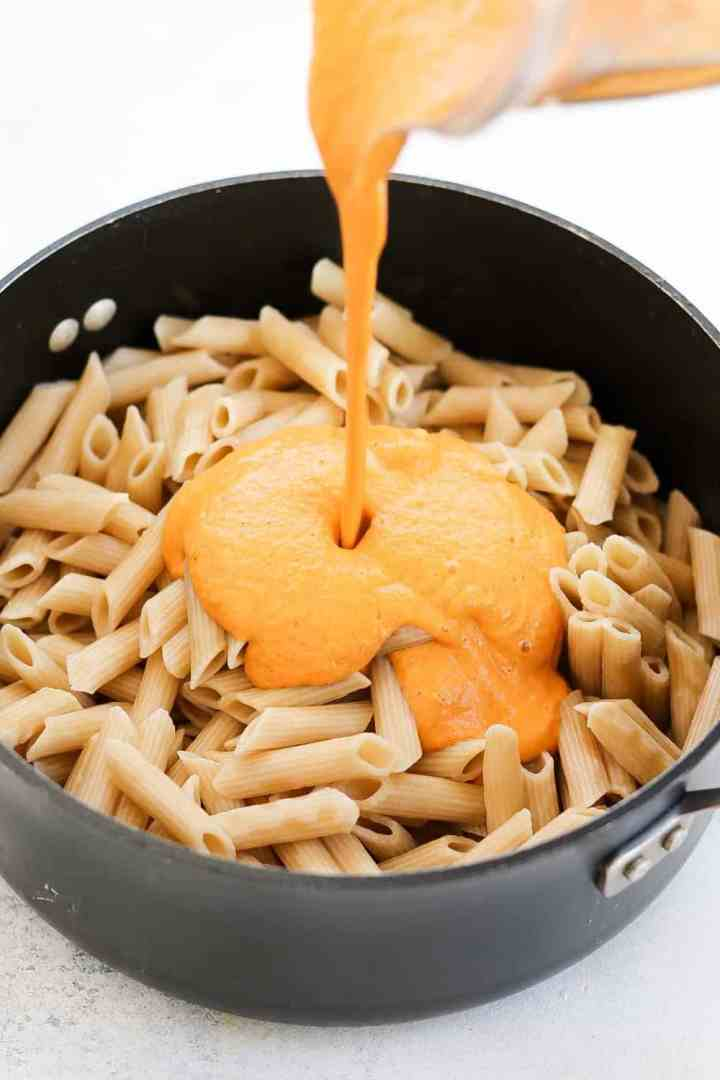 Pouring the creamy vegan pasta sauce on top of pasta in a large black pot.
