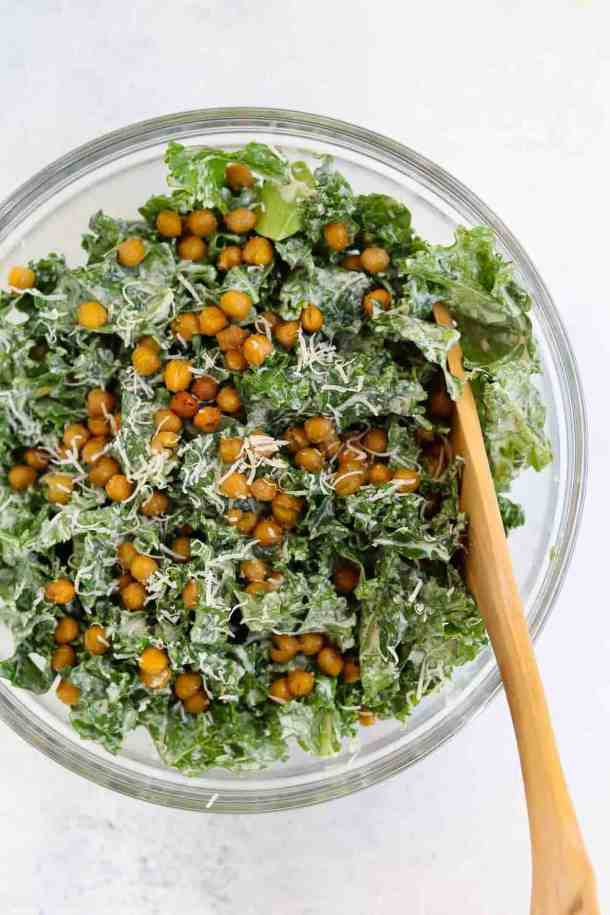 Large glass bowl with kale caesar salad and a wooden spoon on the side.