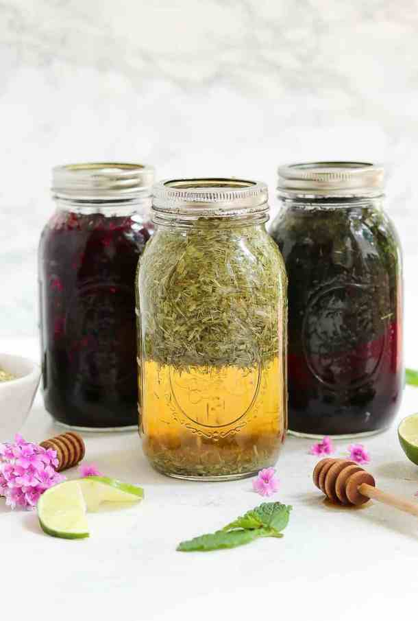 Three mason jars with herbal infusion and lids on top.