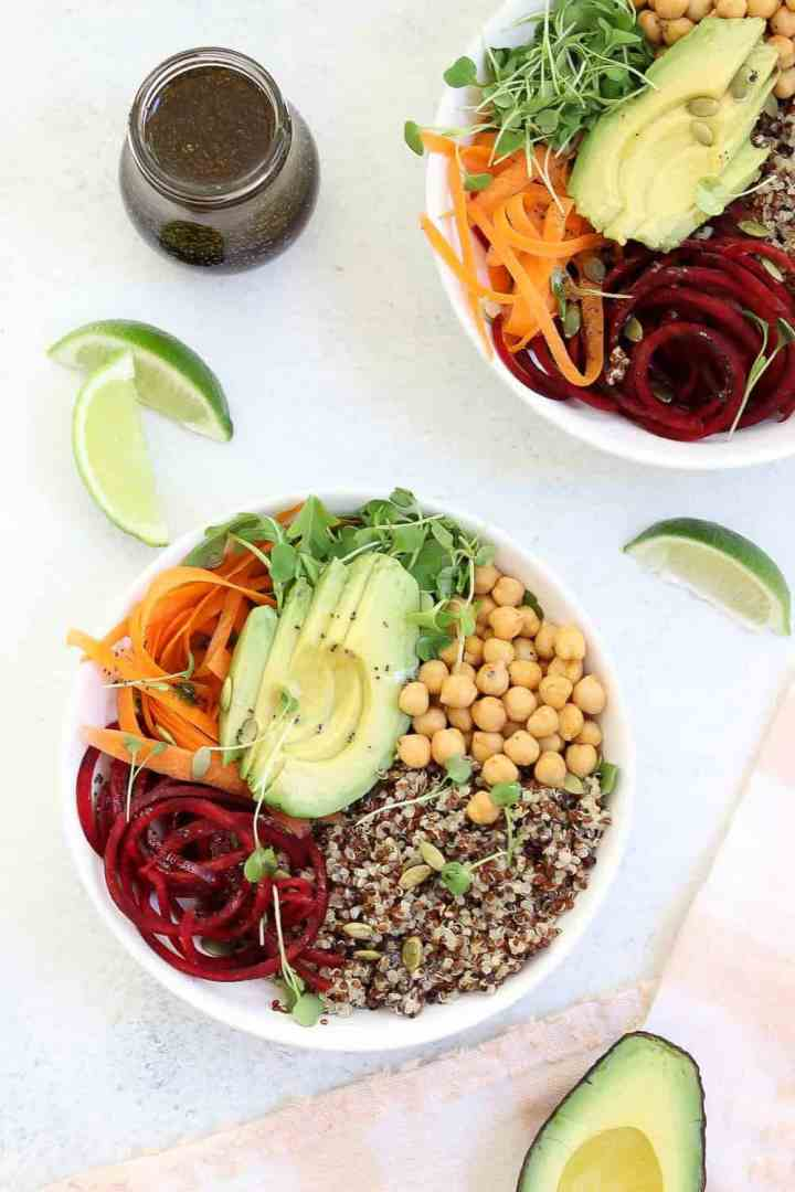 two buddha bowls in white bowls with lime wedges on the side.