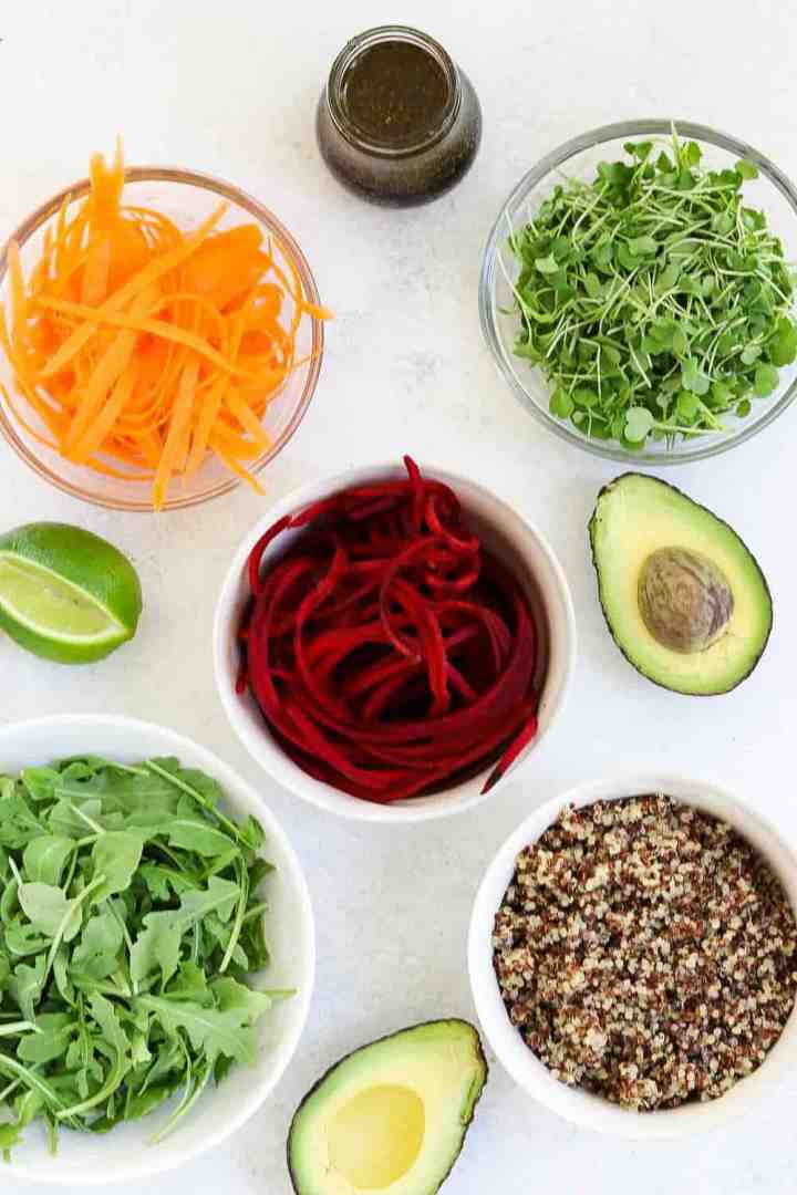 Ingredients for the quinoa buddha bowl arranged in white bowls.