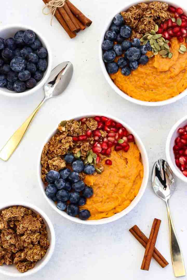 Overhead shot of breakfast in white bowls with granola and blueberries.