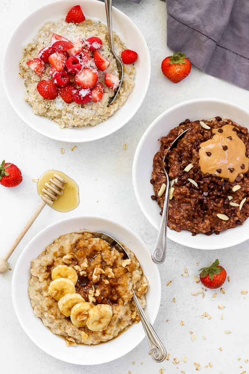 Three bowls of oatmeal on a white backdrop.