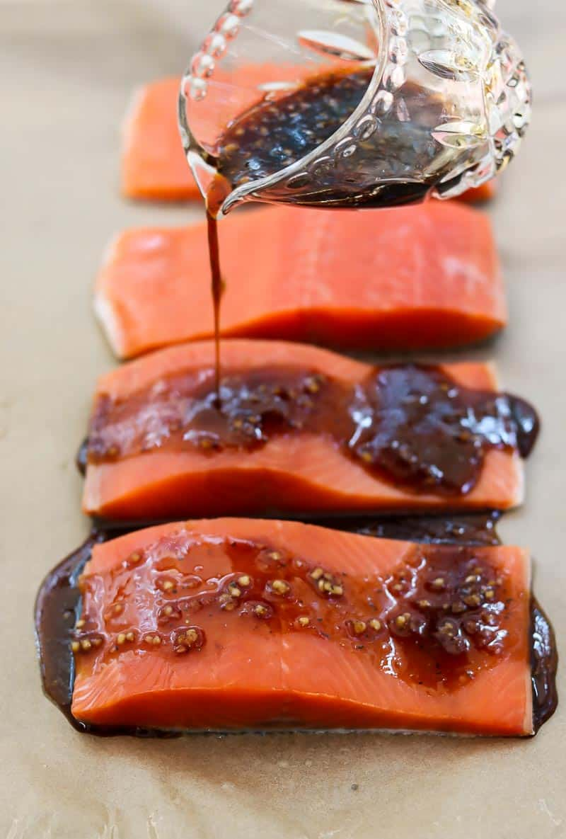 Pouring the maple glaze on top of salmon fillets.