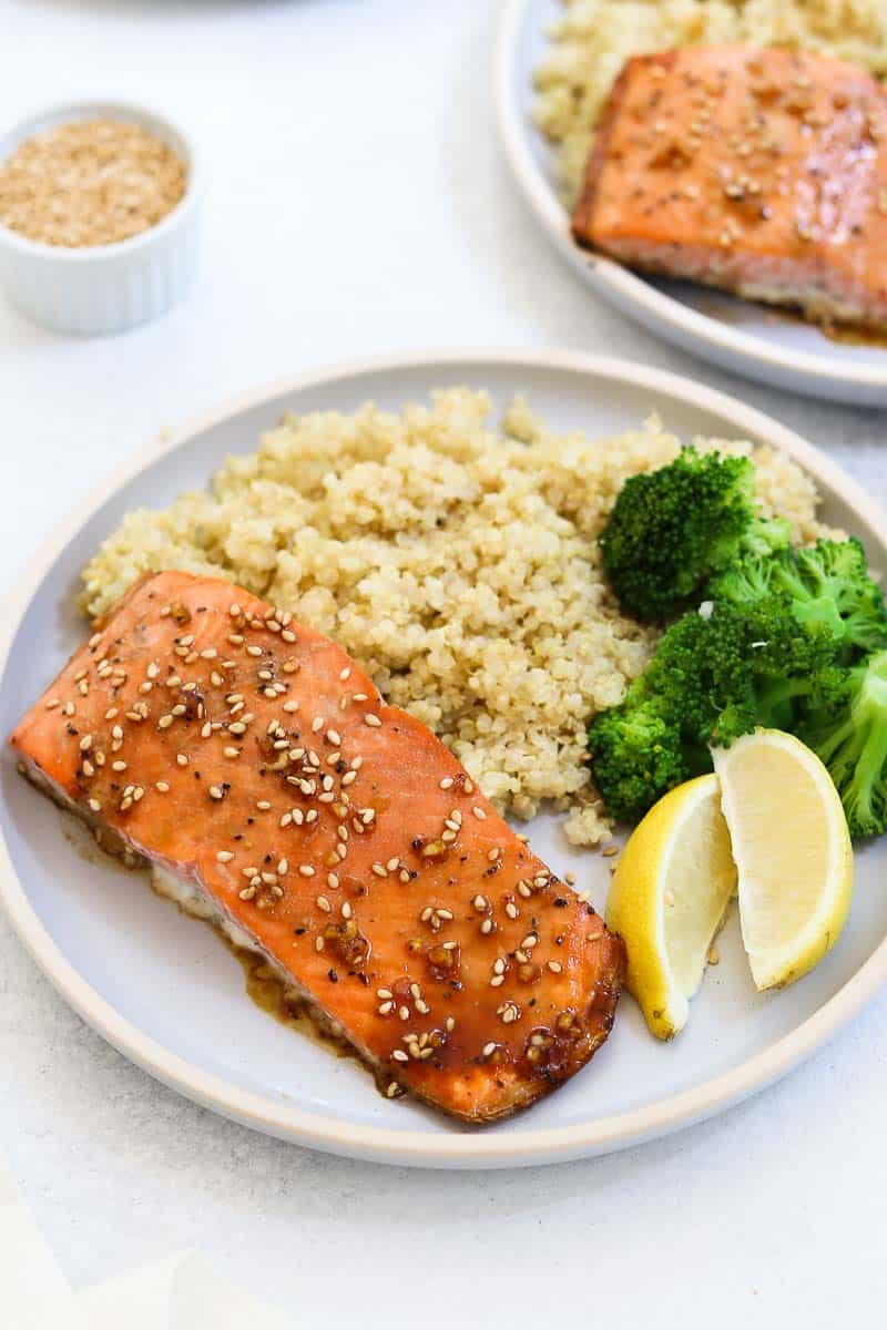 Salmon served with quinoa, broccoli, and fresh lemon.