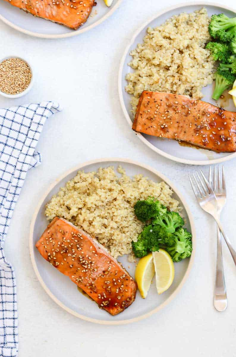 Maple glazed salmon on a blue plate with quinoa, broccoli and lemon.