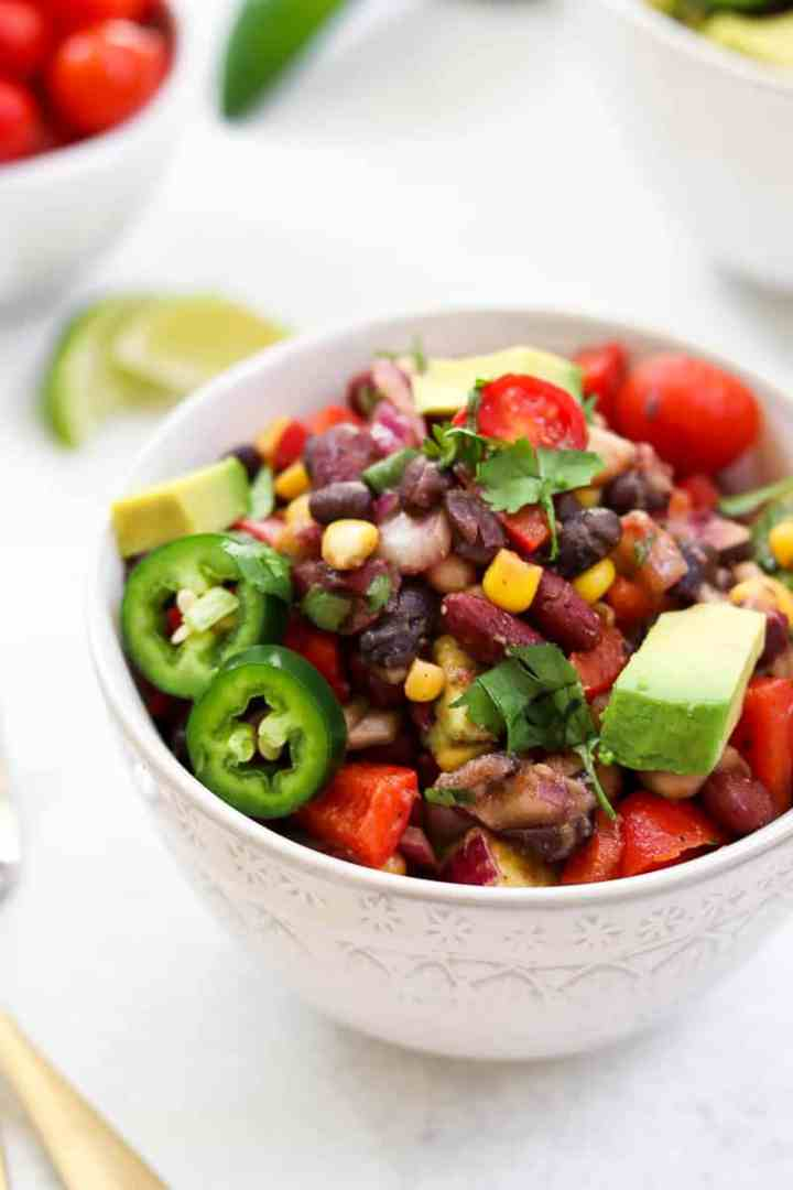 Mexican bean salad in a white bowl with avocado.