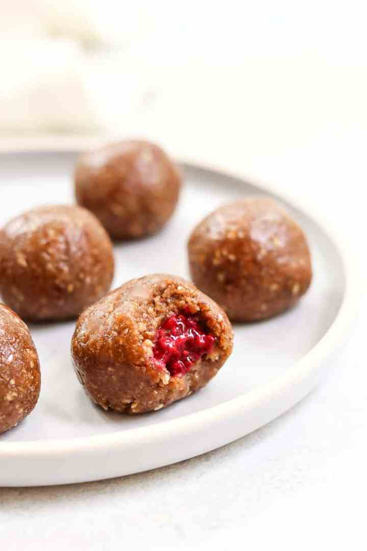 Final peanut butter energy balls with jam on a blue plate.