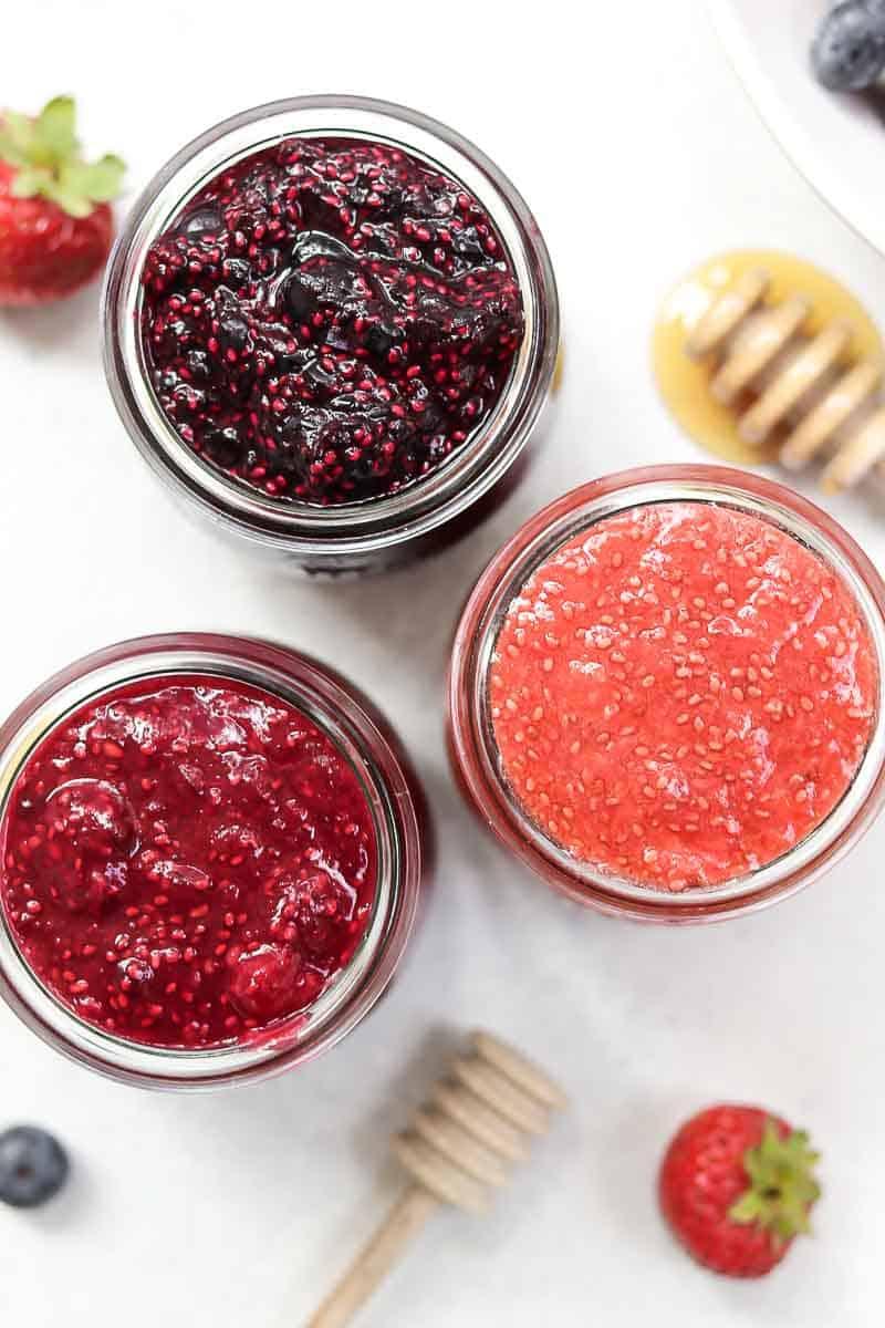 Three jars with berry jam and honey.