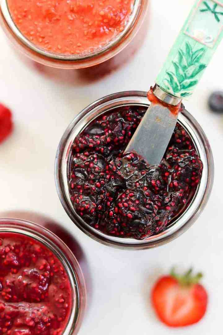 Up close of blackberry chia jam with a small knife.
