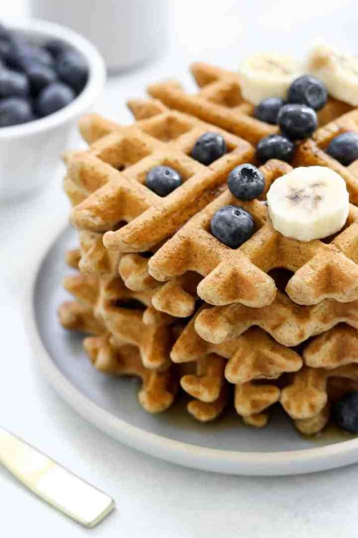 Stack of waffles with berries on top.
