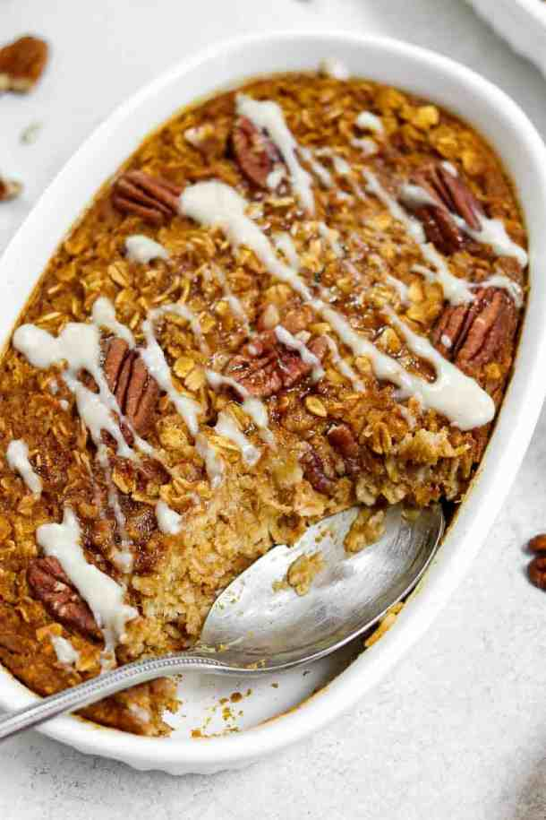Baked pumpkin oatmeal with a spoon in a white dish.