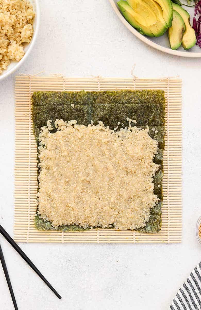 Quinoa and nori on a bamboo mat.