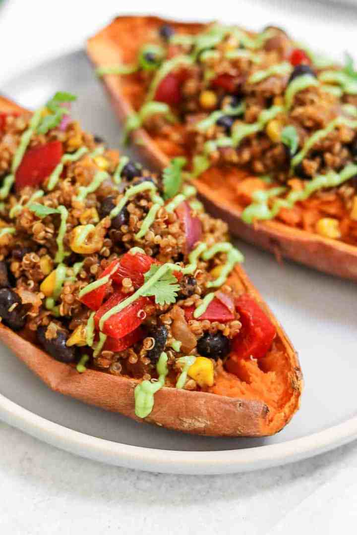 Up close of mexican quinoa stuffed sweet potatoes with avocado sauce.