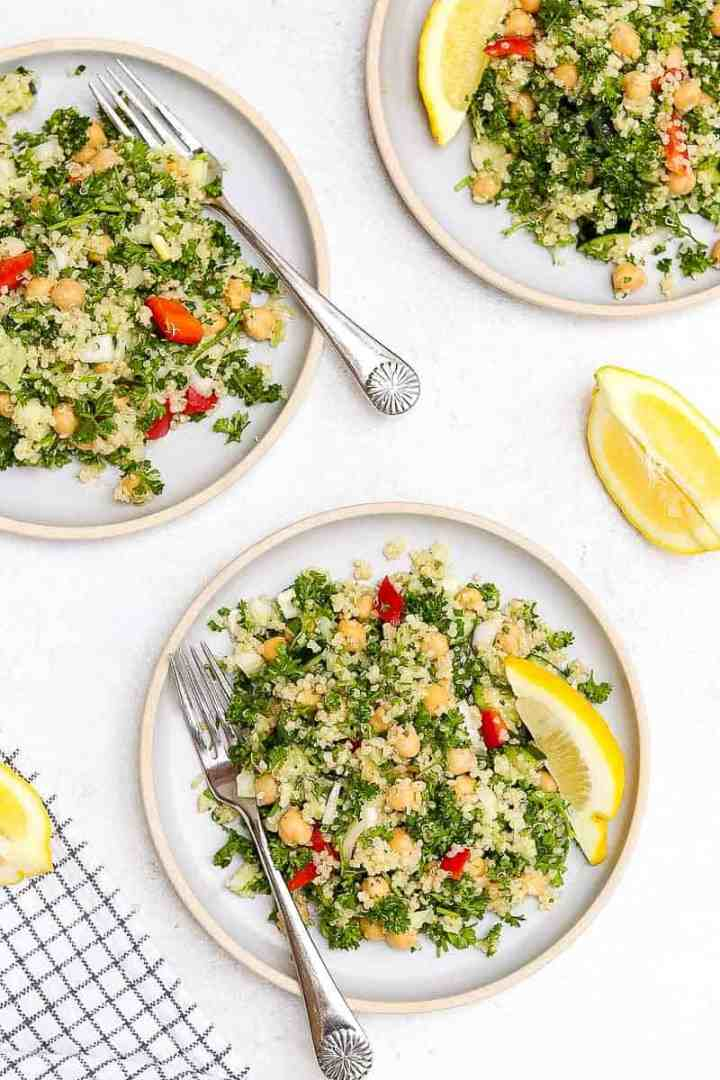 Quinoa tabbouleh salad on three blue plates with lemon wedges.