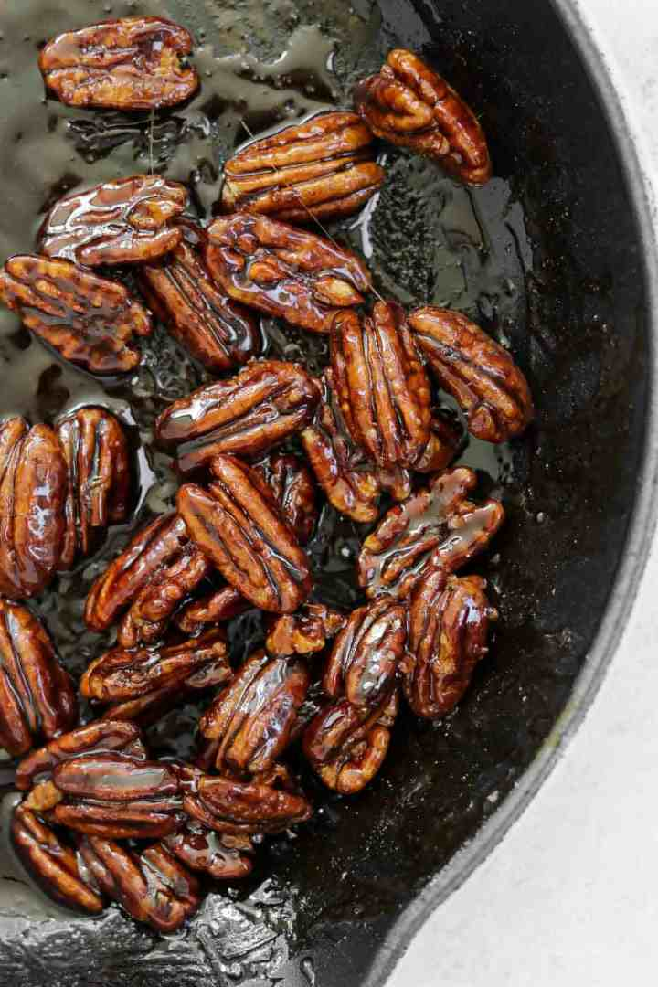 Candied pecans in a black pan.