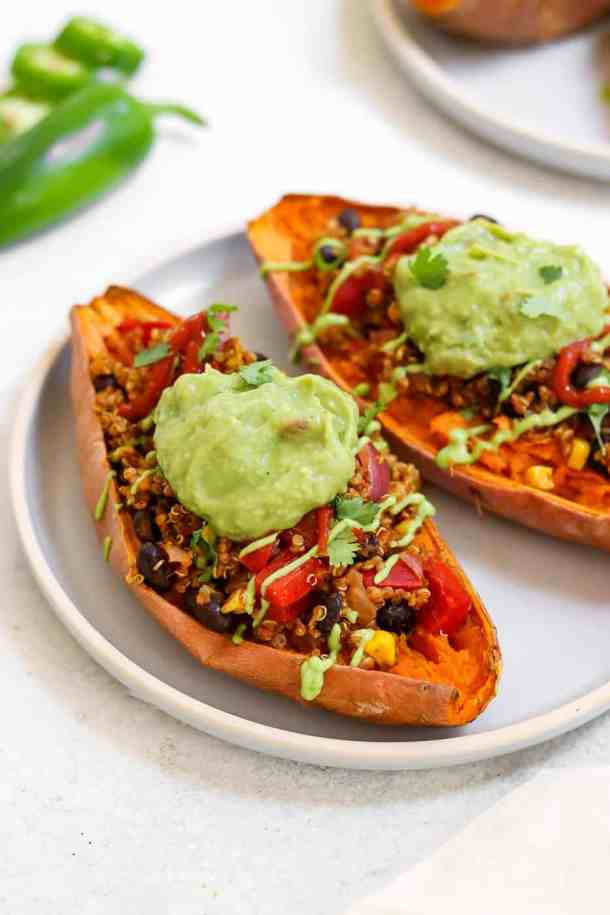 Two sweet potatoes with quinoa and guacamole.