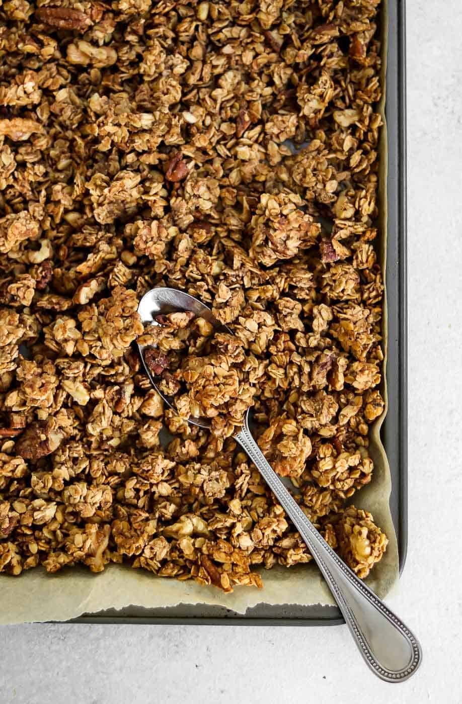 Baked granola on a baking tray with a spoon.