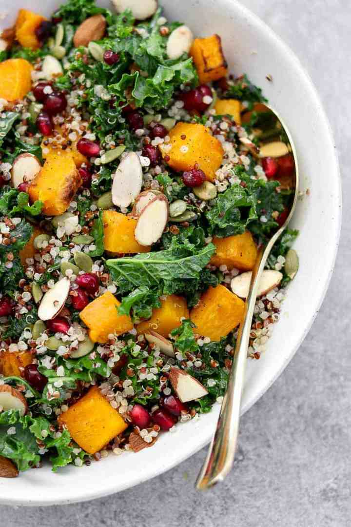 Kale and butternut squash salad in a white bowl with a gold spoon on the side.