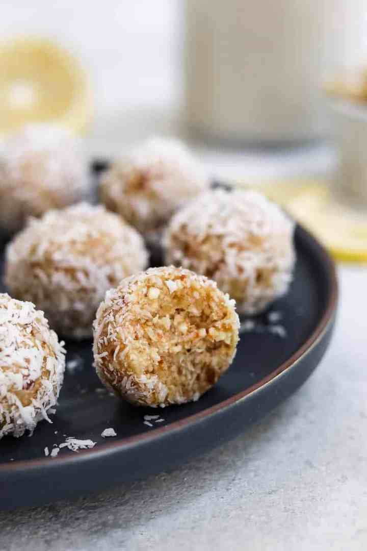 Lemon coconut bliss balls on a dark blue plate with one bite taken out.