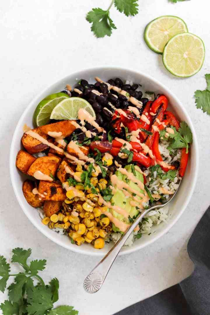 White bowl with sweet potato, black beans and vegan tahini dressing.