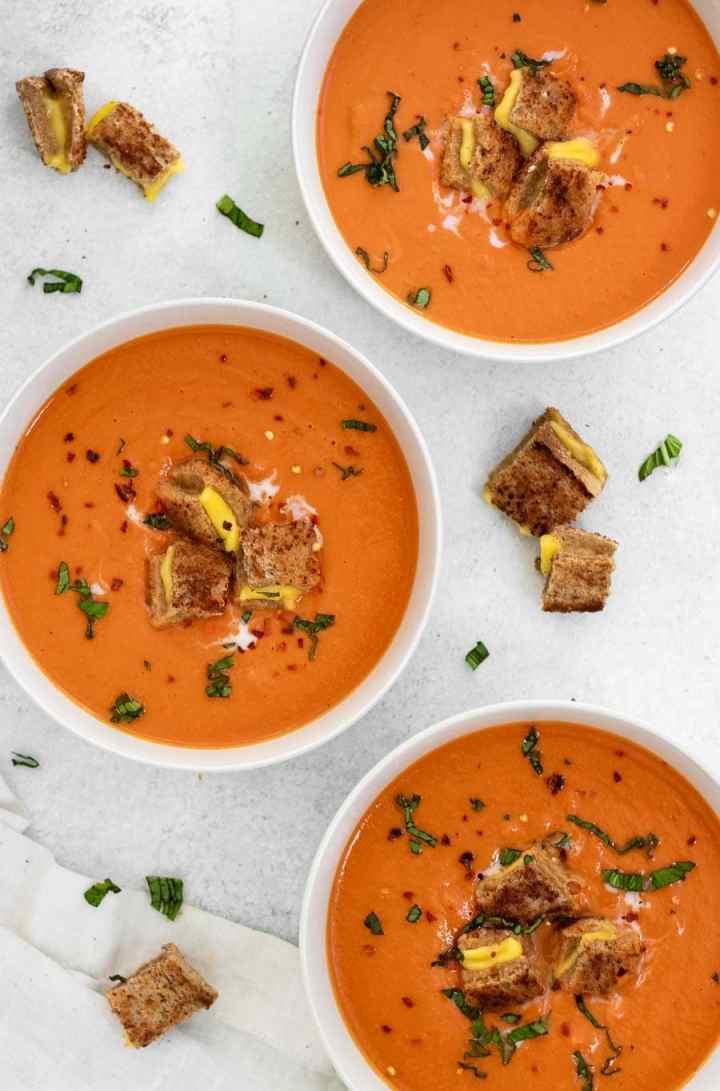 Vegan tomato soup in three white bowls.