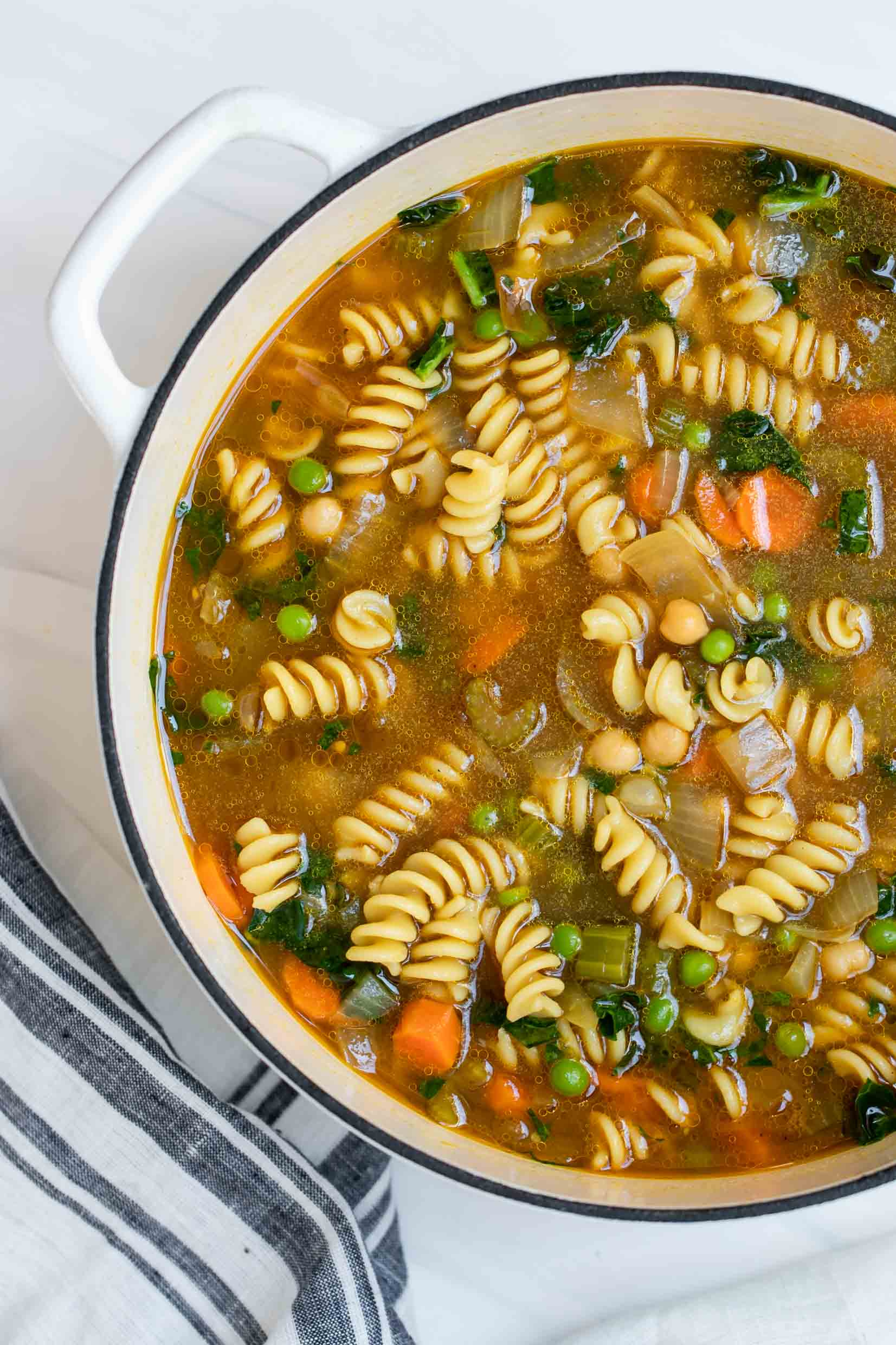 Chickpea noodle soup in a large white pot.
