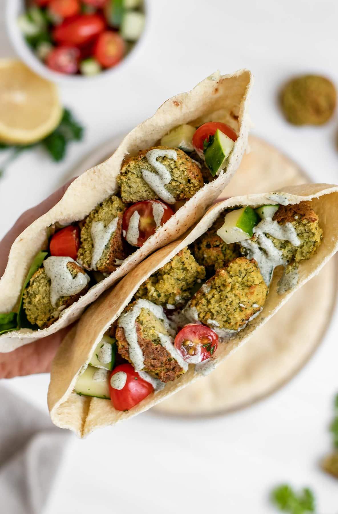 Two pita wraps with vegan falafel, tomatoes, cucumber and hemp dressing.