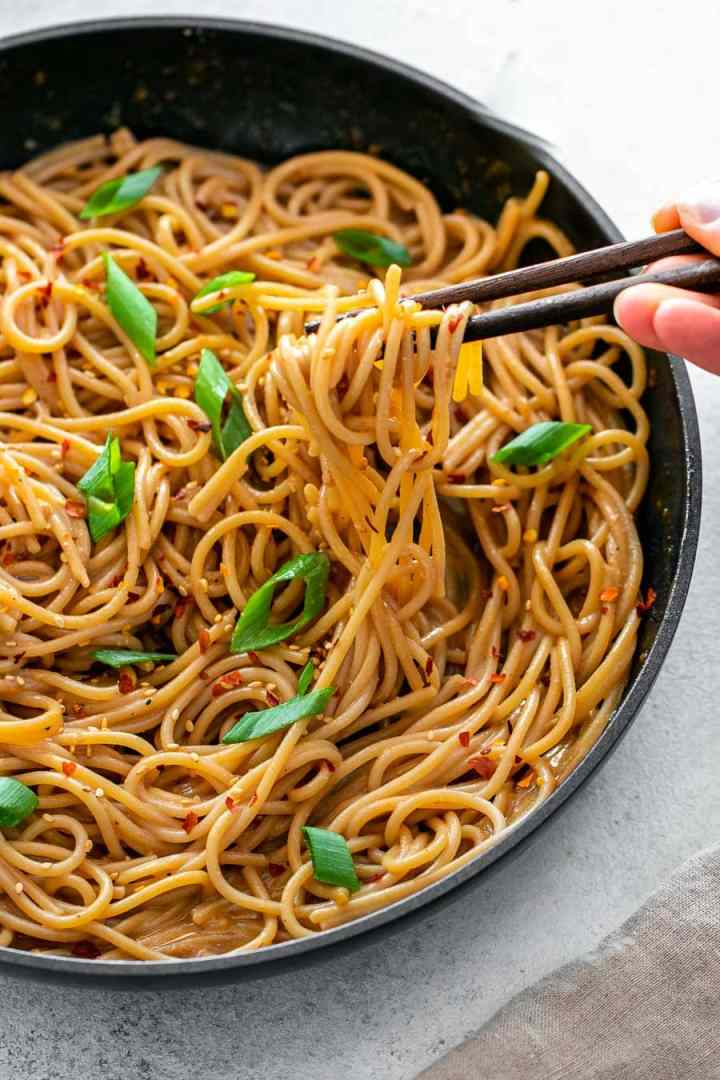 Noodles in a black pan with chopsticks.