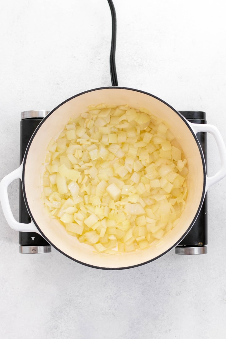 Onions and garlic sauteing in a white pot.