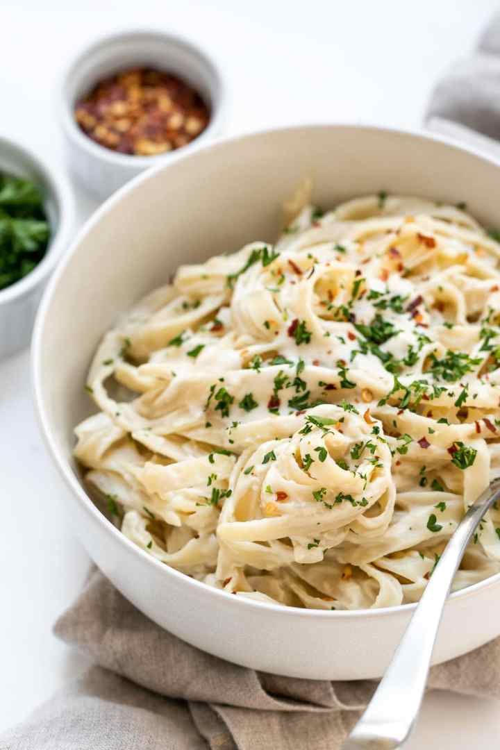 Vegan alfredo sauce recipe on fettuccine with parsley on top.