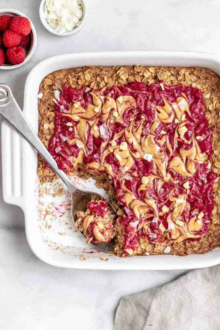 Peanut butter and jelly baked oatmeal in a white baking dish.