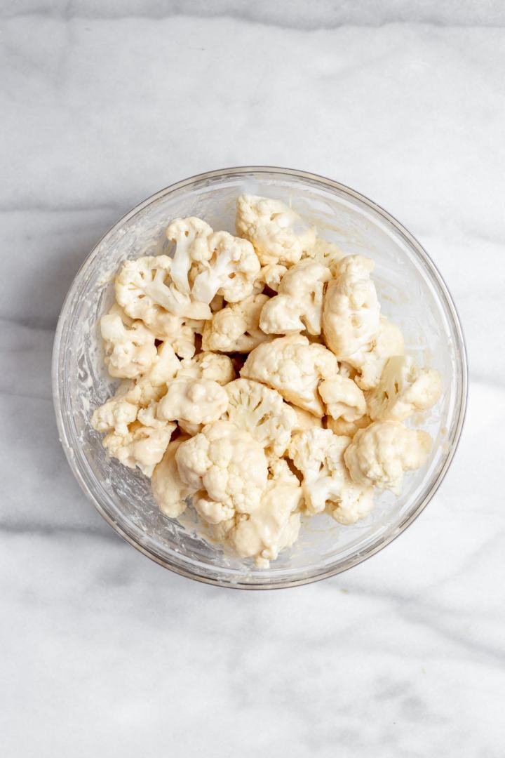Chopped cauliflower in a glass bowl with coating on top.