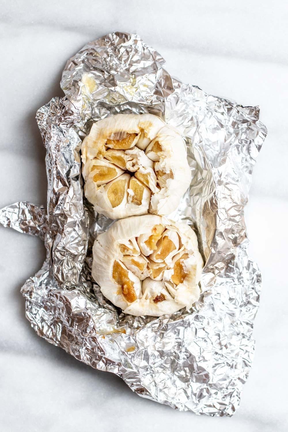 Two heads of roasted garlic wrapped in foil.
