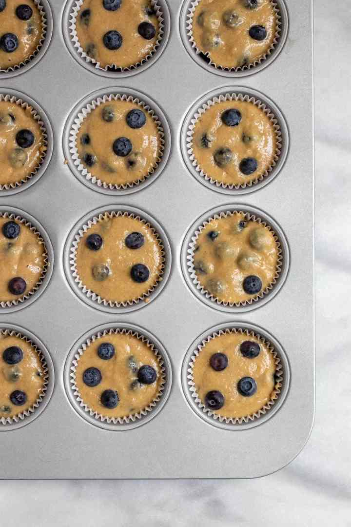 Blueberry muffin batter in the muffin tins.