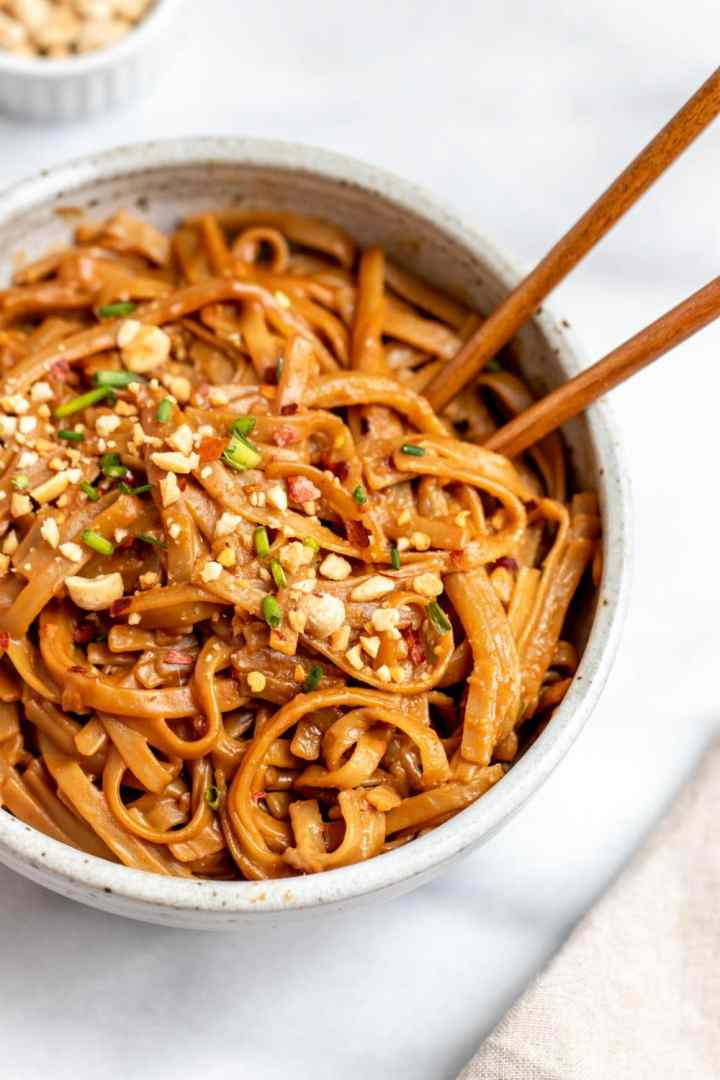 Peanut butter noodles with peanuts on top in a small bowl.
