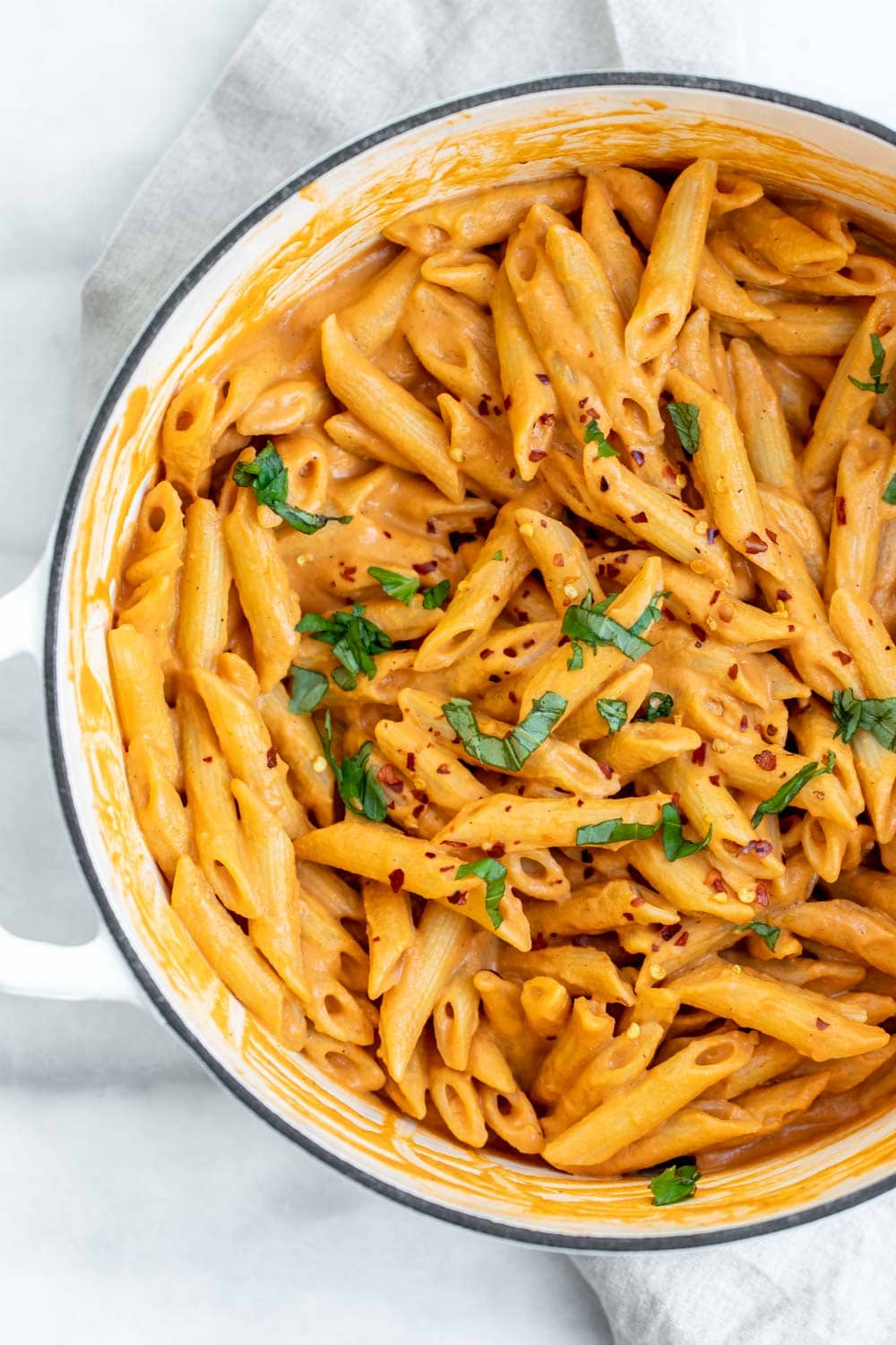 Creamy vegan pasta in a large white pot with fresh basil on top.