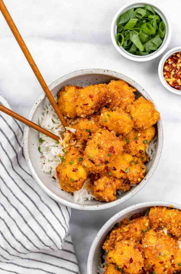Two bowls with orange cauliflower with chopsticks on the side.