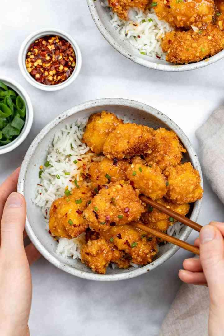 Hands holding a bowl of orange cauliflower with brown chopsticks.