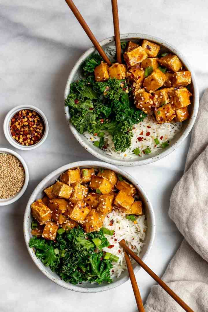 Teriyaki tofu with sauteed kale and white rice with chopsticks in a bowl.