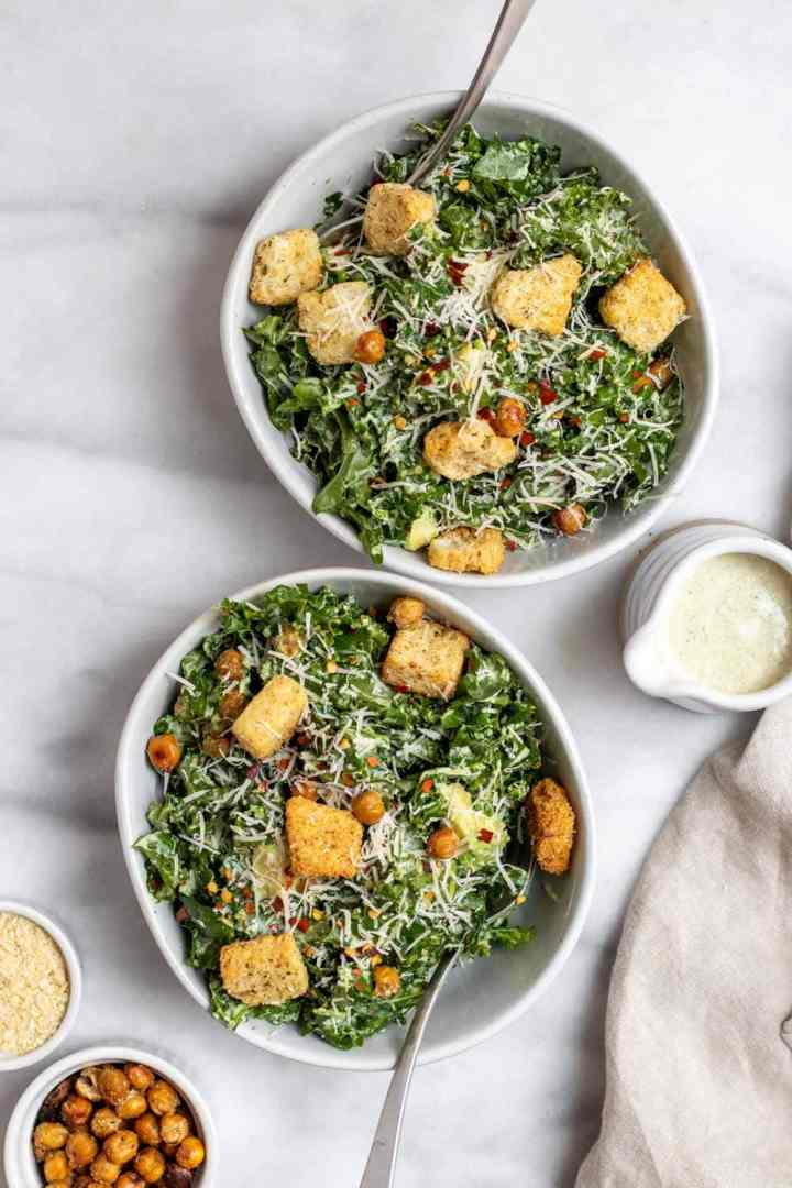 Kale caesar salad in two bowls with forks on the side