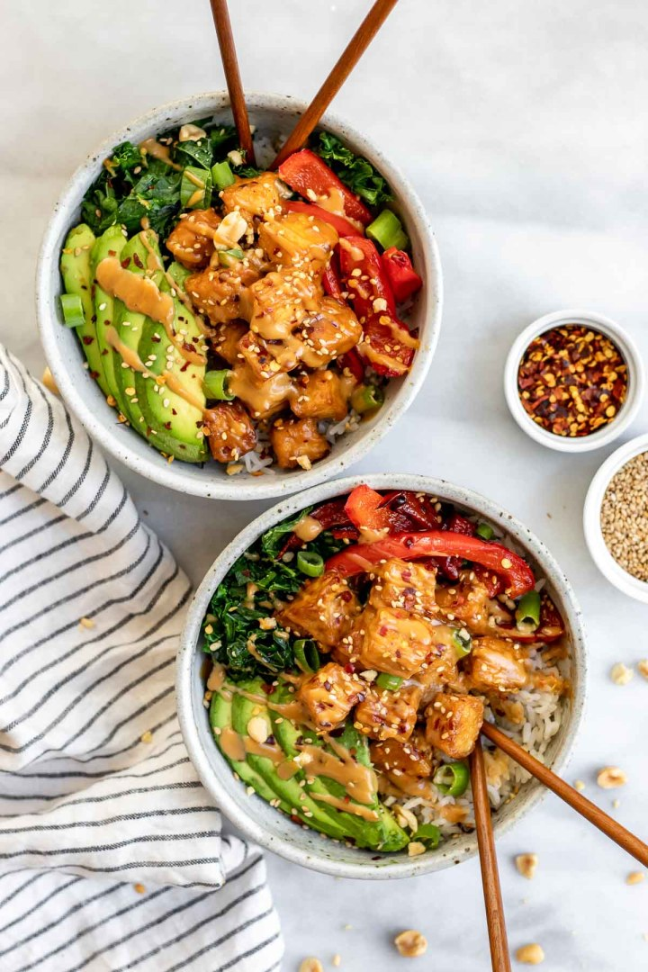 Two buddha bowls with peanut tofu and peanut sauce on top.