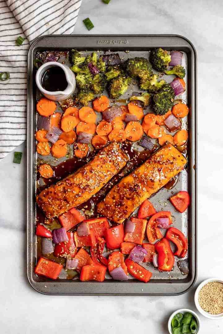 Overhead shot of sheet pan maple salmon with vegetables and sesame seeds.