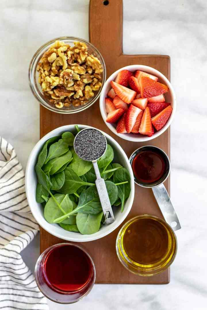 Ingredients for the salad arranged on a wood board.