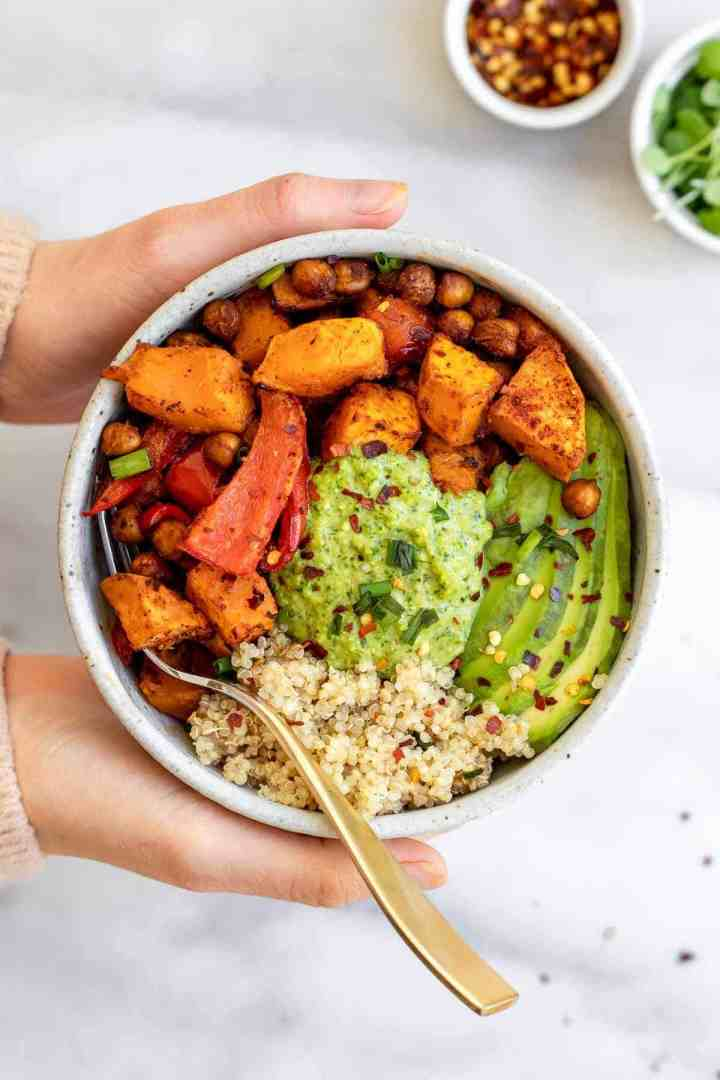 Two hands holding the bowl with the vegan sweet potato and chickpea recipe.