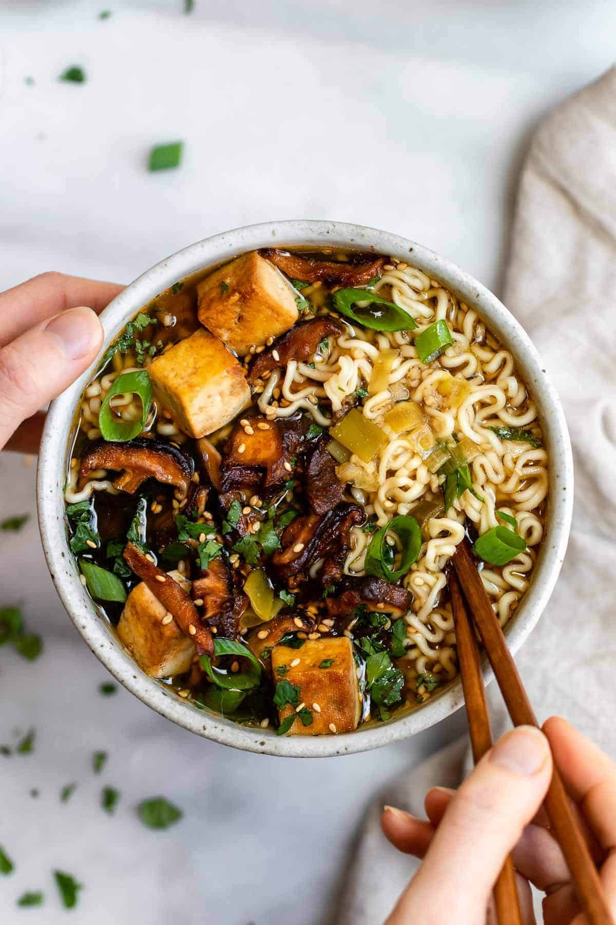 Two hands holding a bowl of vegan ramen noodles with mushrooms.