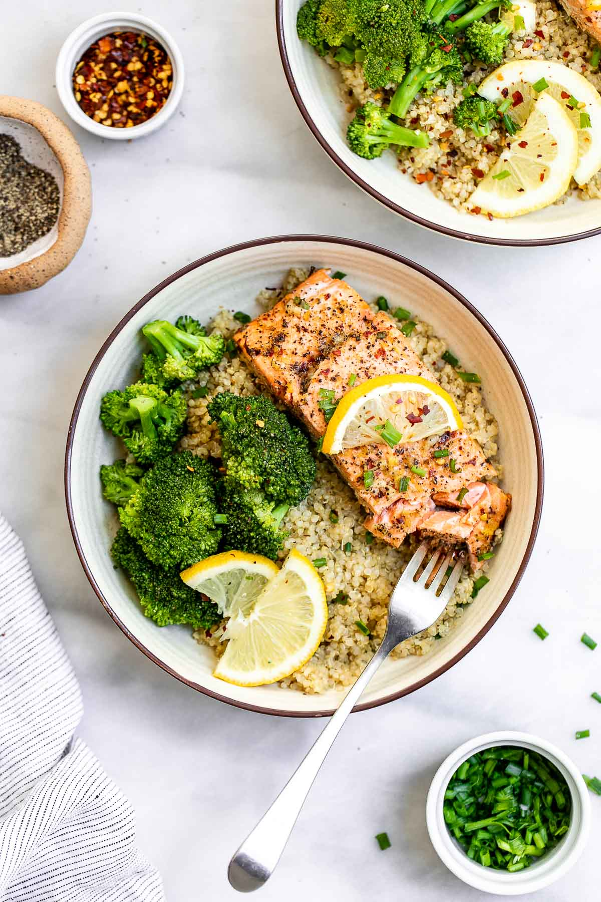 Lemon pepper salmon in a bowl with quinoa, broccoli and lemon wedges.